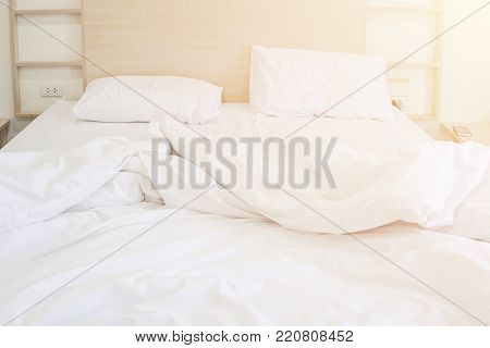 Comfortable bedroom unmade white bedsheet messy and pillow after sleep with sun warm in the morning