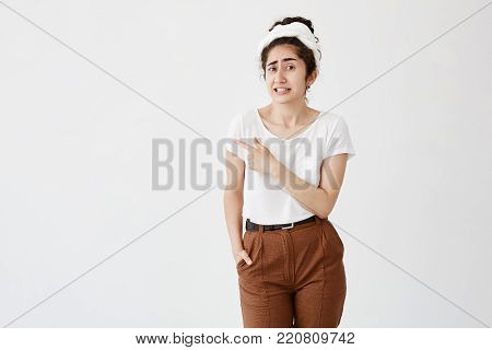 Horizontal portrait of shocked young woman with dark hair in bun eyes clenching teeth pointing sidewards with finger frowning her face. People and emotions concept