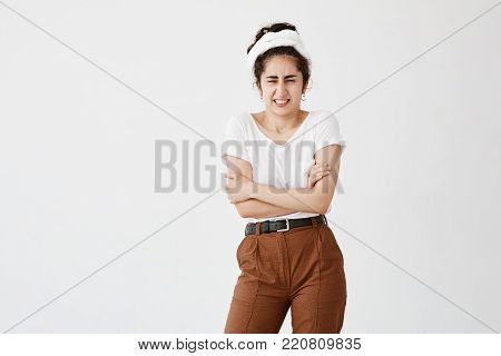 Indoor studio shot of disgusted young dark-haired woman in casual clothes standing in closed posture, keeping arms folded, frowning her face after she saw something awful.