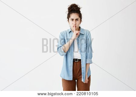 Secrecy, privacy and confidentiality. Frowning young woman with hair in bun in denim shirt and serious strict look holding index finger on her lips, saying shh, demanding silence or asking to keep private information a secret