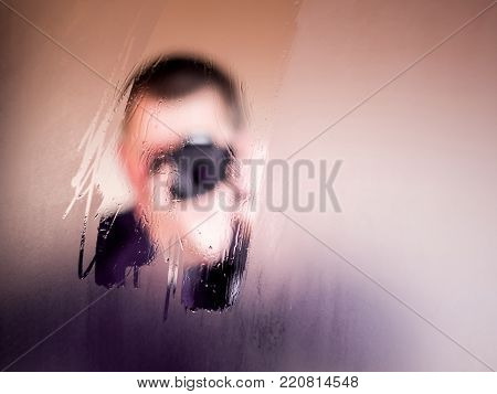 the fuzzy image of the photographer is displayed on the wet mirror