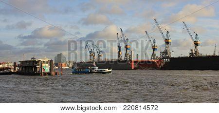 Harbour cranes in Hamburg. Boat on the Elbe.  View from Hamburg Altona.