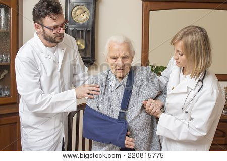 Doctor And The Nurse Lead An Old Sick Woman. Senior Woman With A Broken Arm In A Sling.