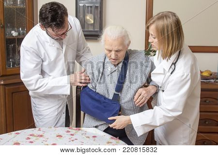 Doctor And The Nurse Help The Old Woman Get Up From The Chair. An Old Woman With A Hand In A Sling.