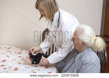 Doctor Puts The Stabilizer On The Wrist Of The Old Woman.