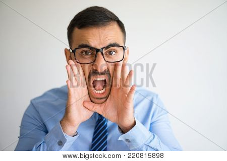 Closeup portrait of excited office worker in glasses opening mouth and shouting loud. Manager announcing important news. Announcement and warning concept