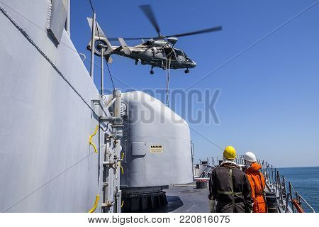 a helicopter provides the defense of a military warship. boarding of a vessel. sailors watch a helicopter dip over a ship. military drill and rescue operation.
