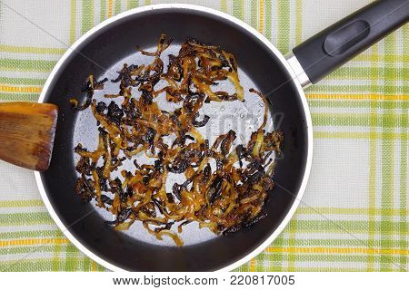 An overhead photo of burnt onion on the black teflon pan. Spoiled unhealthy overcooked burned meal. Onion disgusting leftovers. Messthetics aesthetic concept. Fried bad taste fat food for recycling