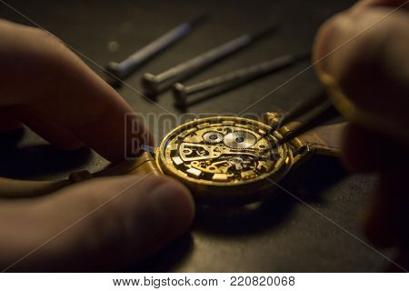 Clockmaker is repairing wrist watch. Close up