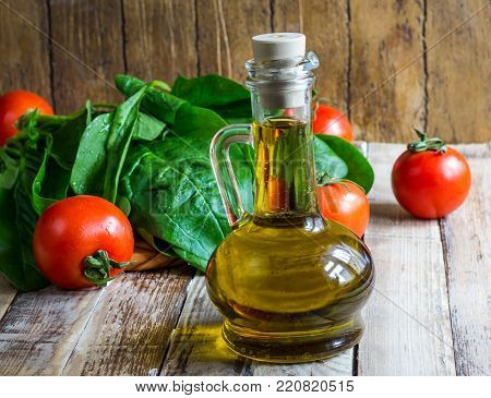 Italian cuisine. Mediterranean cuisine. Tomato spinach leaves and olive oil on wooden table. Recipe Ingredients. Selective focus