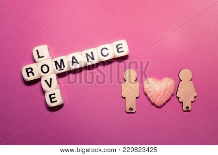 Love romance crossword block text with two wooden figures couple male and female and pink thread heart on pink background. Close up conceptual scrabble letter tiles forming love romance crossword