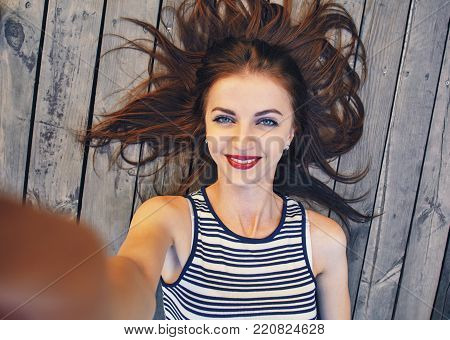 Close up portrait of a young attractive woman holding a smartphone digital camera with her hands and taking a selfie self portrait of herself while networking. Travel and technology outdoors.