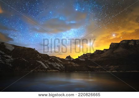 High mountain lake in the northern Caucasus, surrounded by epic rocks and a bright winter starry sky at sunset. Night scenery on long exposure. Magic picture