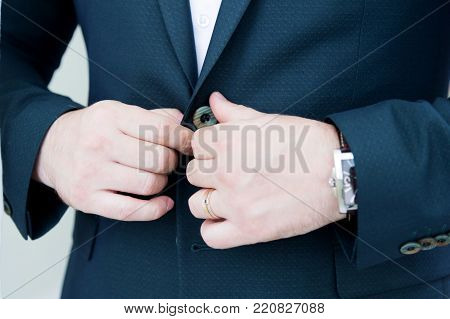 A stalwart newlywed with a beard in a suit fastens the button of his jacket. Super close-up. The concept of business style on holidays