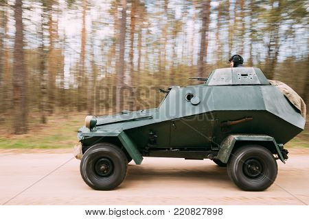 Gomel, Belarus - April 22, 2017: Re-enactor Dressed As Russian Soviet Crew Member Soldier Of World War II Sitting In Russian Armored Soviet Scout Car BA-64 Of World War II Is Driving Along Forest Road