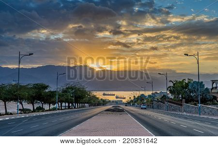 Local street of the Eilat city leading to the Red Sea during colorful sunrise above Jordanian mountains, Middle East