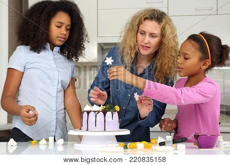 the a children help mom decorate the cake