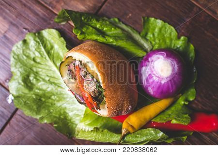 A pie stuffed with meat and vegetables. A sandwich with meat and pickled cucumbers with onions. The sandwich lies on the salad sheet. Chili is on a salad leaf. The violet bow lies behind the sandwich.