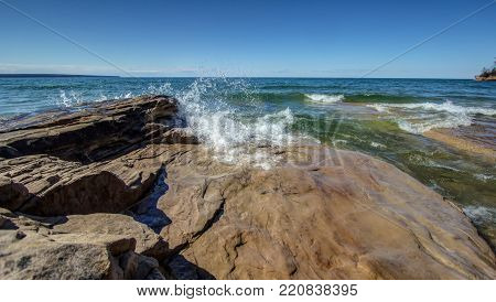 Waves Crash On Michigan Beach. Waves crash on the rocky coast of the freshwater sea of Lake Superior on a beautiful sunny summer day with a blue sky horizon.
