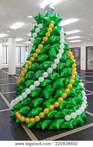 Creative Christmas spruce made of inflatable balloons of green color in the foyer of Opera House