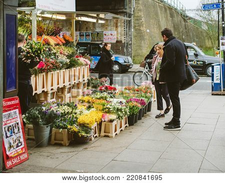 LONDON, UNITED KINGDOM - MAR 10 2017: Couple buying flowers at flower florist kiosk on the street in London early in the morning
