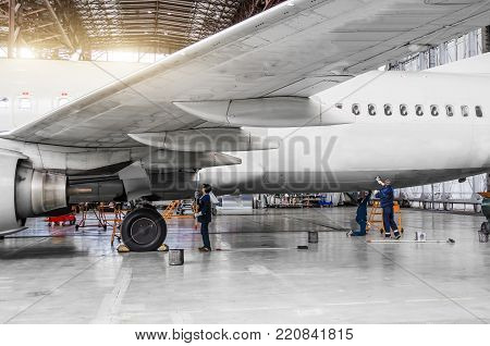 Several people wash the aircraft in the hangar for maintenance, view of the chassis, wing and tail