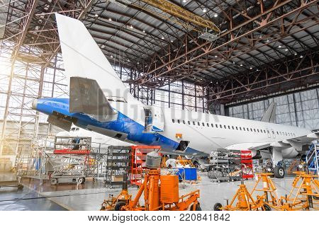 Passenger aircraft on maintenance of engine repair, among the jacks, a view of the tail and the rear of the fuselage in airport hangar