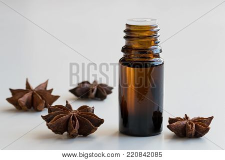 A dark bottle of star anise essential oil with star anise on a white background