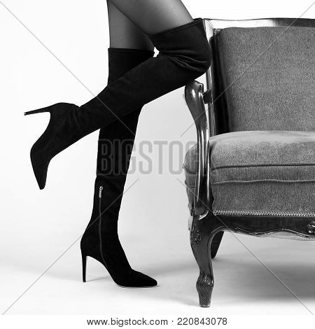 A girl in black suede boots near an old chair