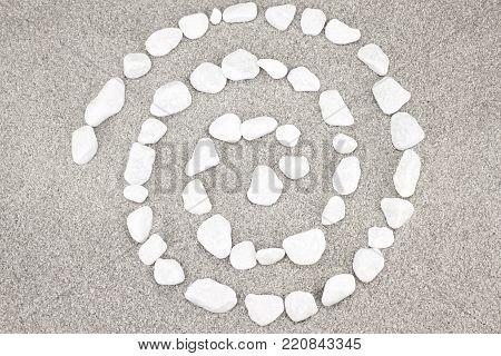 Spiral white pebble stones on gray sand poster