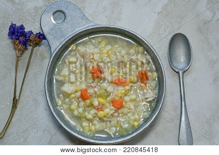 Chicken Corn soup with rivels in metal soup bowl.  It is an Amish classic soup recipe and includes chicken, corn, onion, carrots, celery and homemade dough rivels.