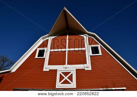 The front of a restored red hip roofed barn with an extended peak and hay loft doors.