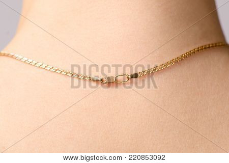 Clasp of a gold chain on the neck beauty macro