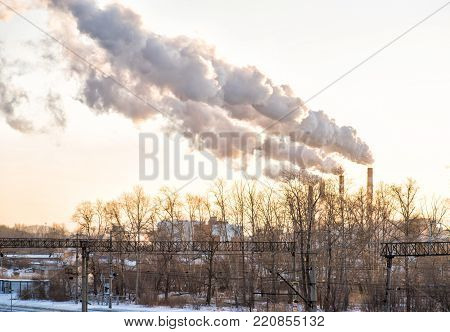 railway station in industrial area with smoking chimney