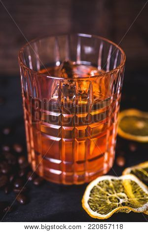An ice cube floats in alcohol in a glass. A glass with whiskey on a wooden background. Close-up of alcohol in a glass. Whiskey or bourbon is poured into a glass. Dried lemon slices and coffee grains lie on the table.