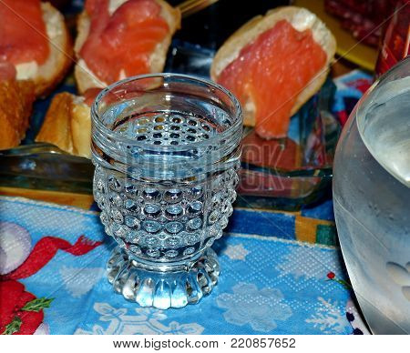 Glass of of cold vodka against a background of sandwiches with salmon. Decanter with vodka. Natural food, appetizer. Gorgeous home appetizer under a glass of vodka.