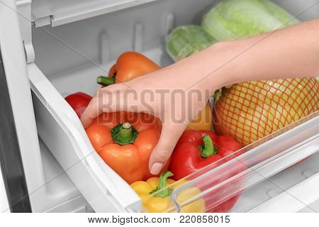 Woman taking pepper from refrigerator, closeup