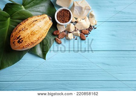 Cocoa pod and products with leaves on wooden background, top view