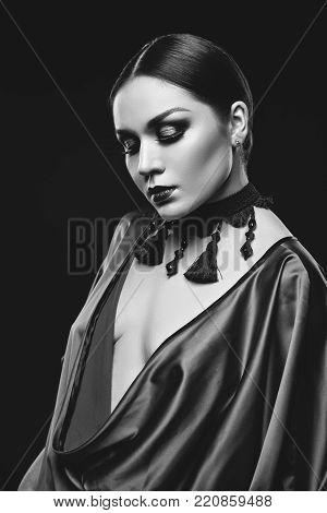 closeup portrait of beautiful young woman with balck hair and dark smokey eye makeup wearing silk blouse. studio beauty shot. copy space.