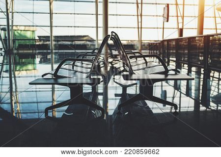 Side view of multiple metal seats inside of waiting hall of modern railway station depot; two rows of seats on reflective floor of waiting room in contemporary airport terminal with glass facade