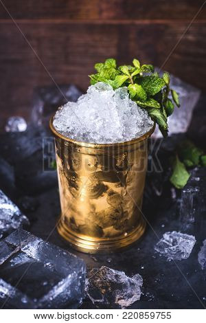A small iron bucket stands on a table with ice. The ice in the tin can is decorated with mint. Crushed ice in a tin can on the table. Ice cubes lie in the background.