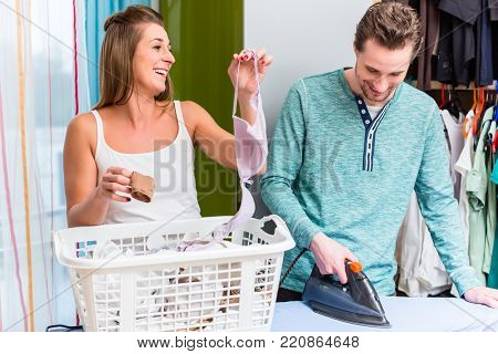 Young couple, woman and man, sharing housework and doing the laundry together