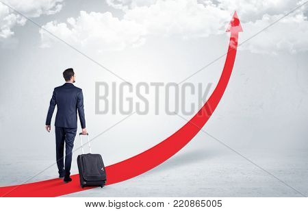 Young businessman with back leaving on the red arrow carpet to the skies with luggage on his hand
