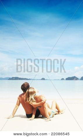 Young couple relaxing on a resort's white sand