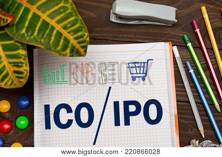 A Notebook with Business notes initial coin offering ICO vs IPO Initial Public Offering with office tools on yellow blue background. Concept of the choice of IPO or ICO ?