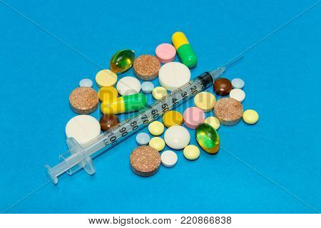 Opioid epidemic .Opioid Pills. Drug abuse Concept - different colored pills and syringe on a blue background.
