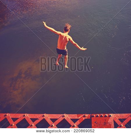 a boy jumping of an old train trestle bridge into a river toned with a retro vintage filter effect on a hot summer day