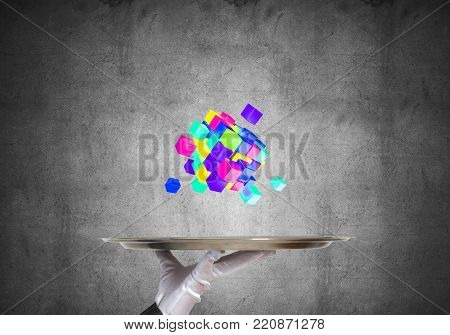 Cropped image of waitress's hand in white glove presenting multiple cubes on metal tray with gray wall on background. 3D rendering.