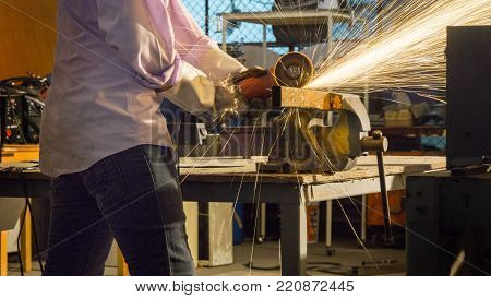 worker uses grinding cut metal, focus on flash light line of sharp spark,in low light