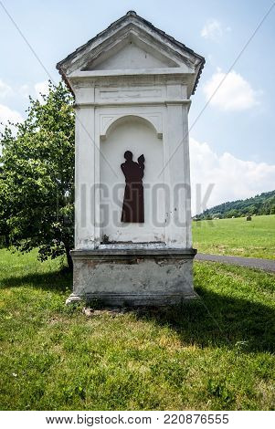 column shrine with tree on the background, meadow and narrow road near Milesov village in Ceske stredohori mountains in Czech republic